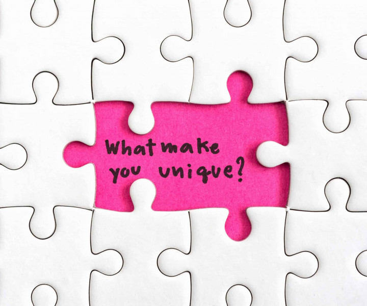 Jigsaw puzzle piece with two missing and hand writing letters word what make you unique and question mark, Quotes business concept